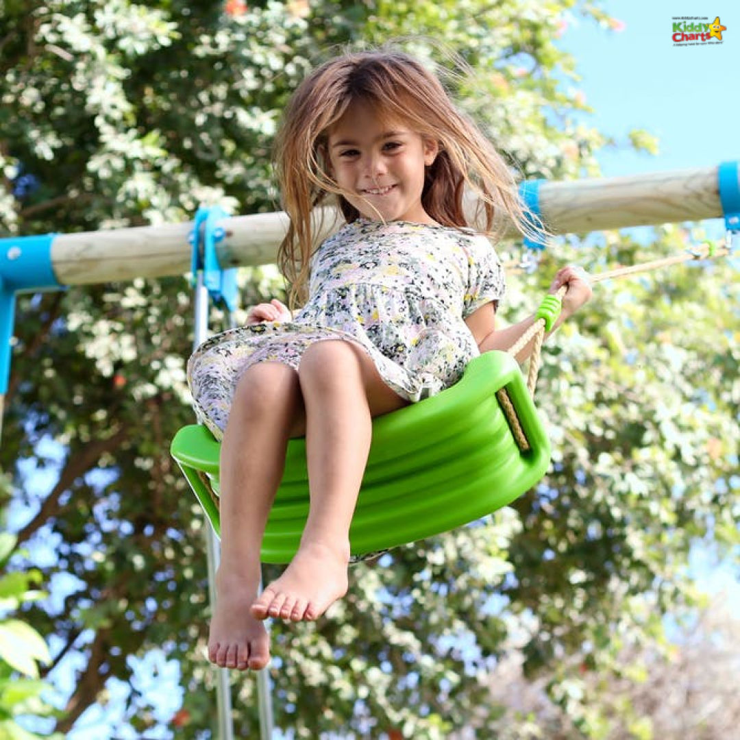 Young girl flying high on a swing with a green seat.