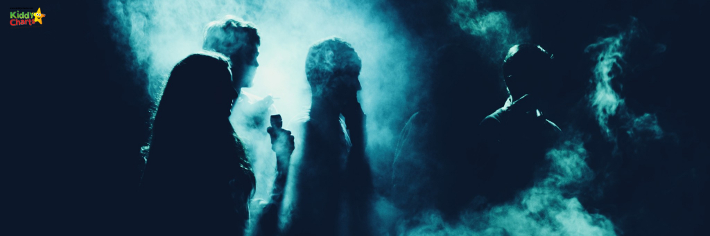 Ghostly figures standing about in the dark with smoke around them.