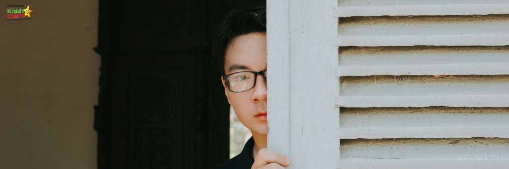 Man with glasses peeping out from behind a door.