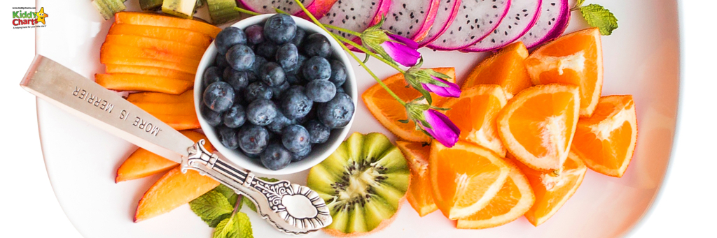 A plate of fruit and a silver spoon.