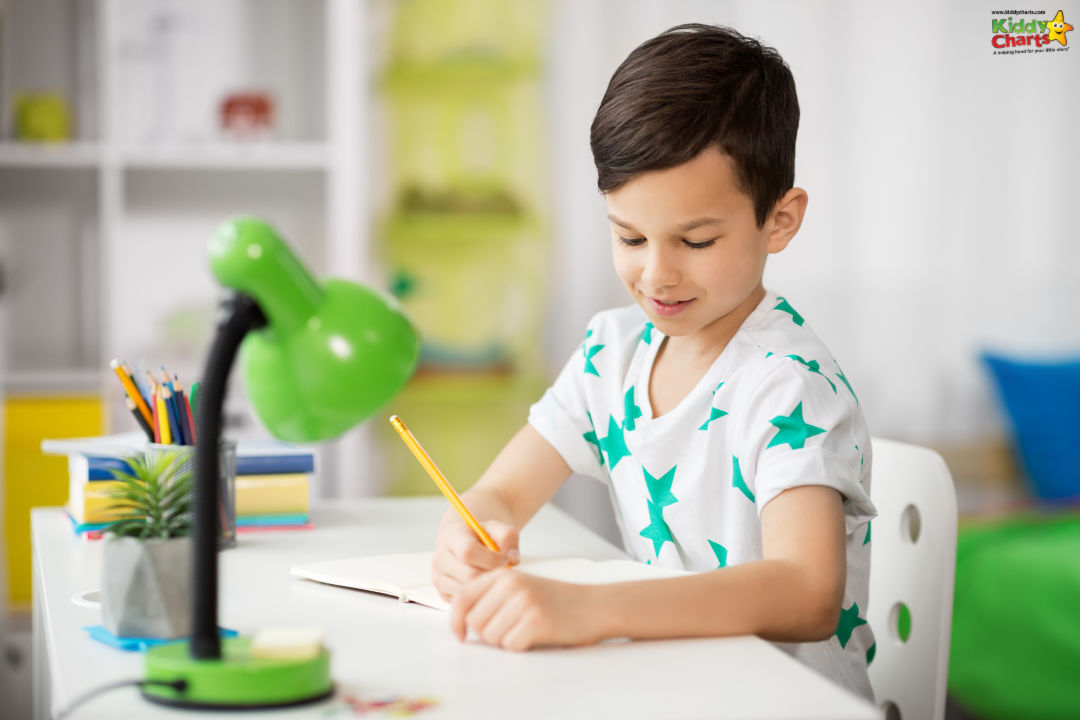 schoolboy sitting on at desk writing in a notebook positive writing prompts