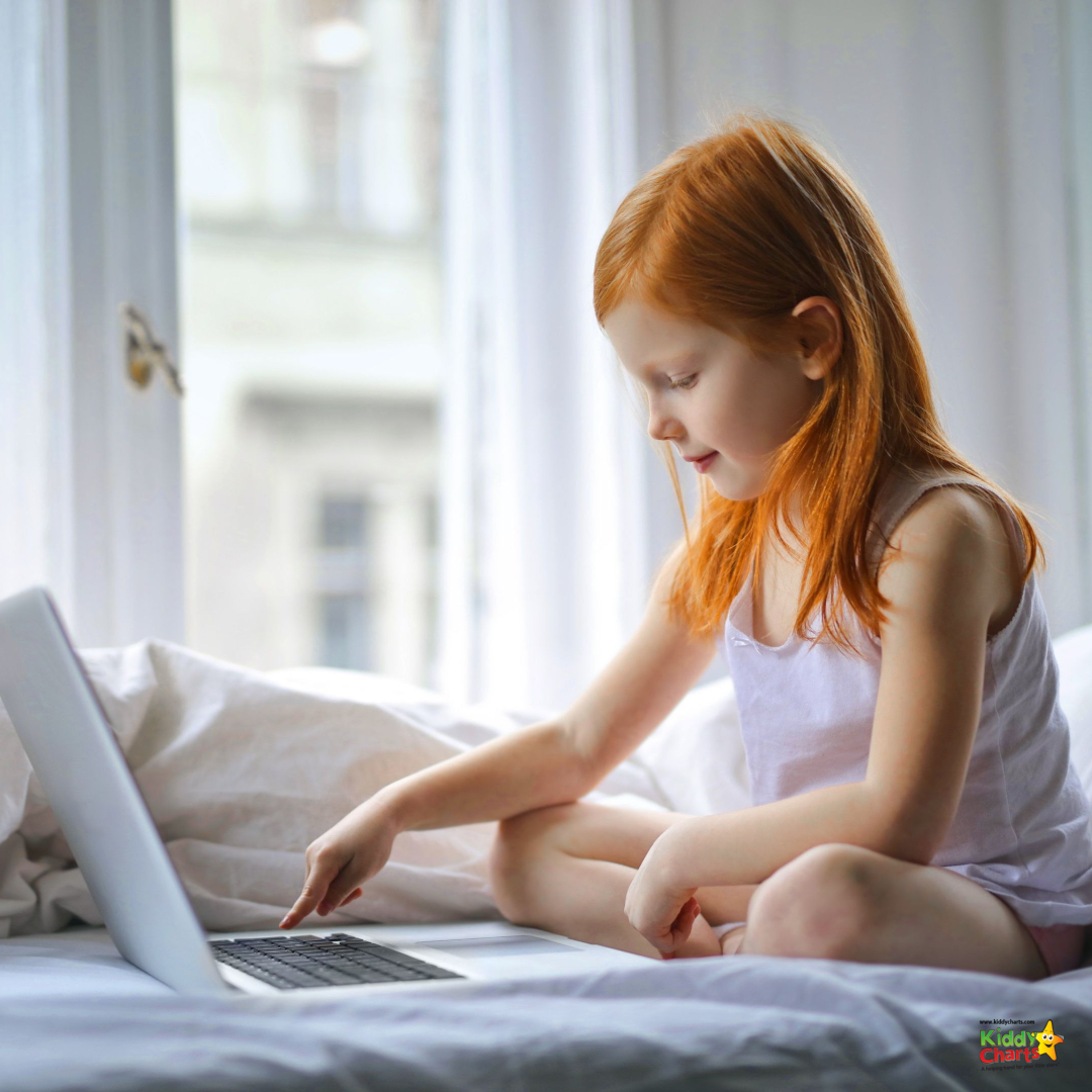 Red haired girl sitting using laptop on bed.