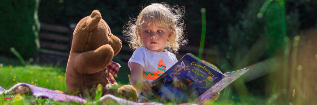 child reading a book next to her teddy bear