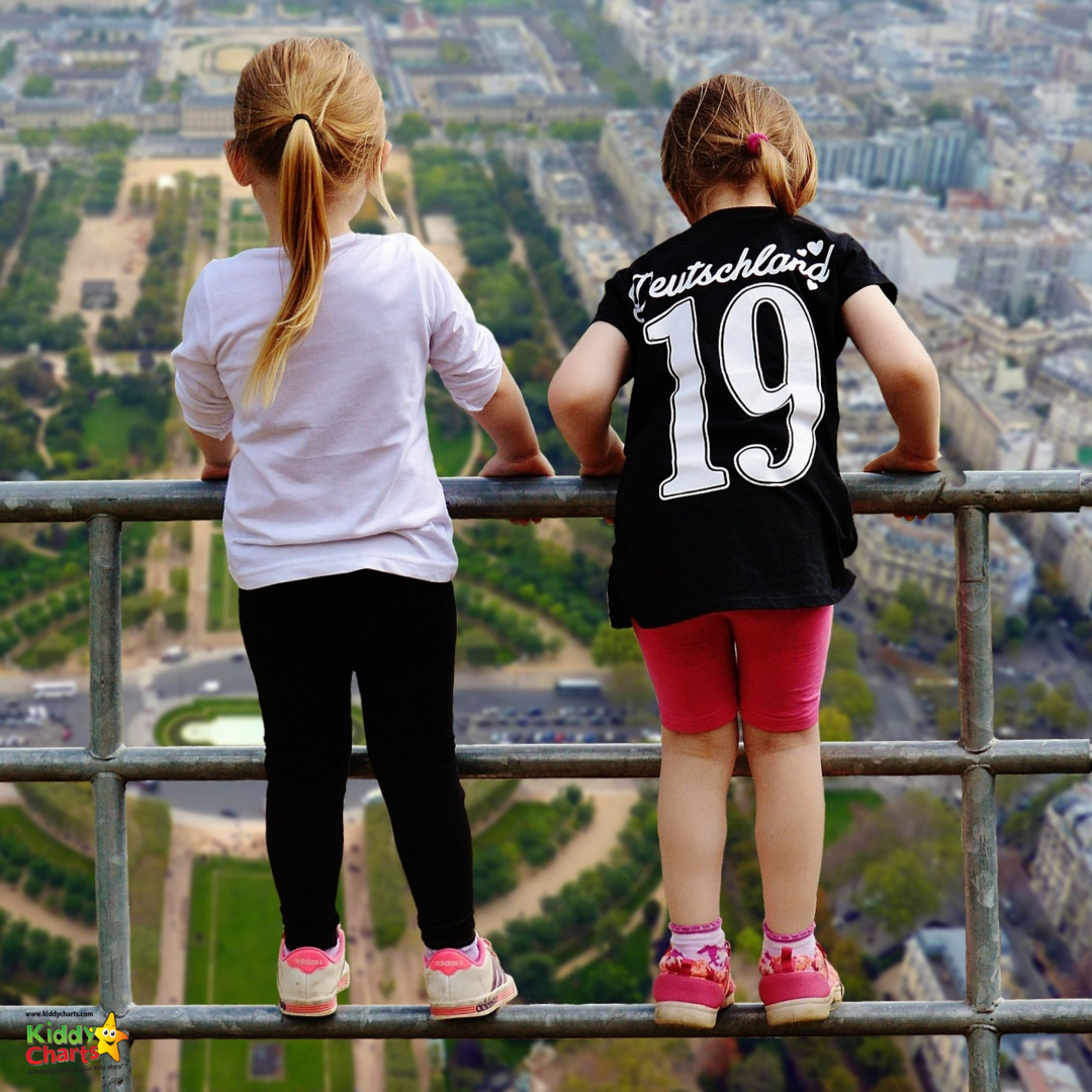two kids looking down from a balcony