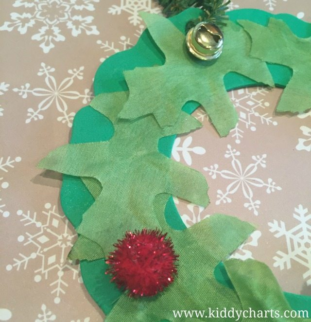 Close up of our Christmas Wreath craft...holly berries and a bell, and don't forget those leaves either.